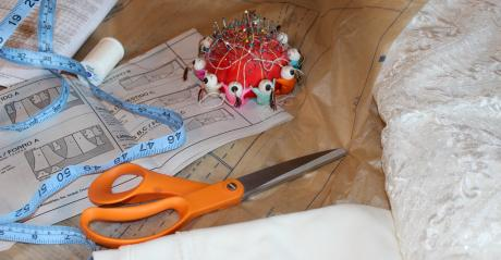 Close up shot of wedding dress fabric, sewing cushion, measuring tape, and scissors