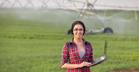 farm woman with laptop and irrigation