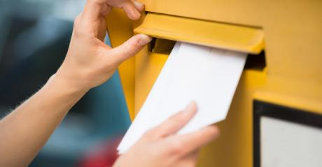 Close-up of hands inserting a white envelope into a yellow mailbox