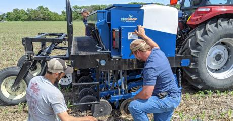 Two men looking at Interseeder machinery