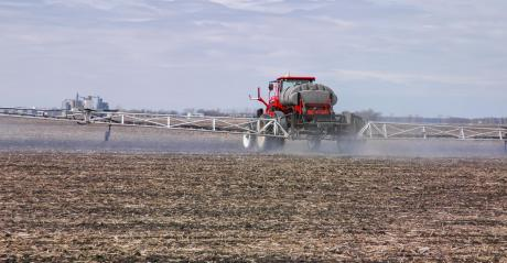 A tractor spraying herbicides on a field
