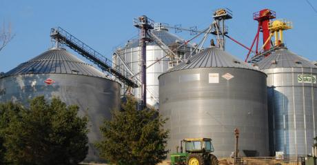 grain bins with tractor in front.