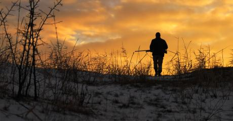 sillouette of man with gun walking on snowy ground with sun setting