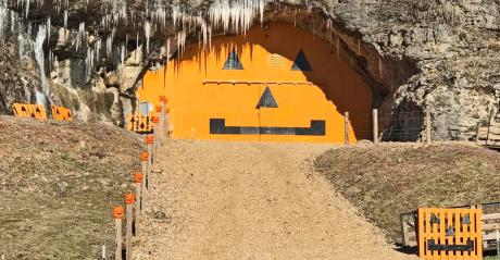 an orange jack o lantern painted on a huge door tucked into a hillside at Cave Pumpkin Patch