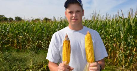 Nathan Bush holding two ears of corn