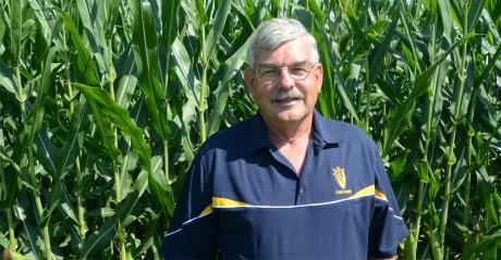 Lynn Chrisp standing infront of corn plants.