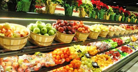 colorful variety of apples, oranges, poinsettia plants in store display