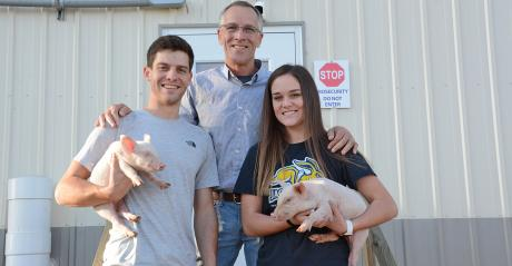 Karl Schenk and his children, Karl II and Kyra, stand in front of their nursery barn holding piglets