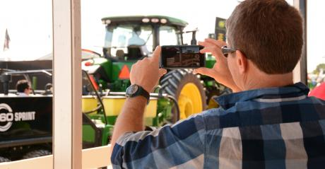 man taking photo of tractor using cellphone