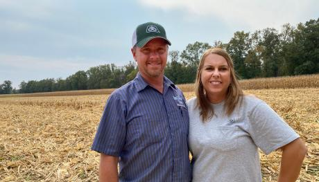 Husband and wife stand in corn field.