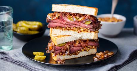 Roast beef sandwich on plate with pickle