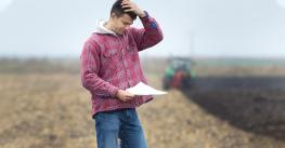 young farmer with hand on head looking worried
