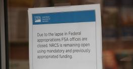 A paper sign reading 'Due to the lapse in Federal appropriations FSA offices are closed' is taped to a glass office door