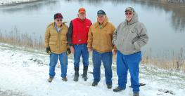 4 men at NRCS watershed project structure