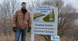 Matthew Romans  stanfing by  a sign that says this farm is enviromntally verified