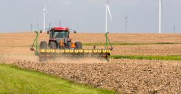 Planter working in a corn field with wind turbines on horizon