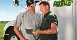 Deere client with Deere support person looking at tablet
