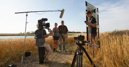 A video production crew films Lisa and Philip Volk on their farm