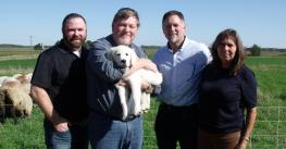 Greg Babcock holding dog, Freedom Belle, awarded to him through Operation Farm Dog. He is standing with 2 men and a woman