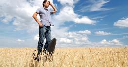Man standing on office chair in a field looking for direction
