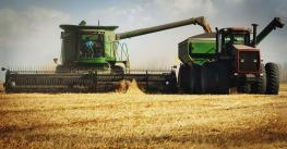 Harvesting Combine with Grain Cart beside it.