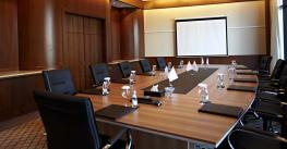 A boardroom table with black comfy chairs.