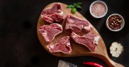 Raw fresh Lamb Meat ribs and seasonings on wooden cutting board.
