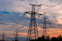 Steel transmission towers in evening or morning light.