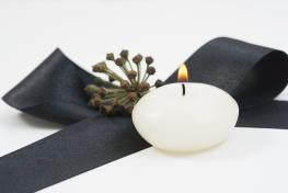 Single white candle with black ribbon.