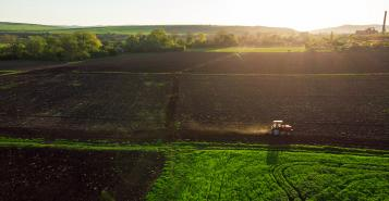 Aerial view of tractors working on the harvest field.