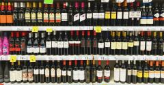 Some shelves with a big variety of wine bottles.