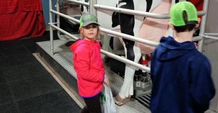 Two kids by robotic milking display, one with back to photographer and one looking at photographer