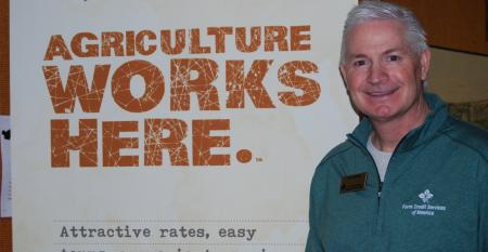 Doug Burns standing infront of Agriculture works here sign
