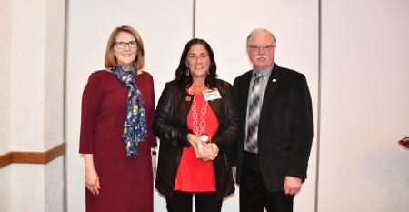 Sharon Toth, UDIM CEO, (left) and Jim Reid, Michigan dairy farmer and UDIM President, (right) present the 2019 Excellence in Dairy Promotion award to Ramona Ann Okkema-Clark of Blanchard.