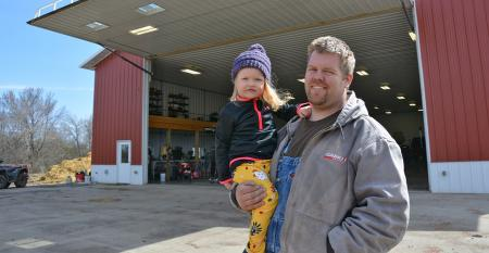 Jason Tolzin holds his daughter, Jailey by shop by Lester Buildings