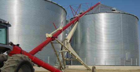 A tractor-driven auger transfers grain from a tray at ground level to the top of a storage bin