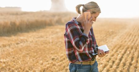 female farmer with smartphone and tablet in field