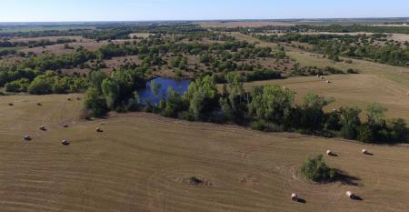 aeriel view of farmland with bales of hay, trees and a pond