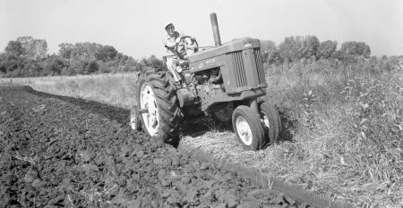 old photo of tractor pulling moldboard plow