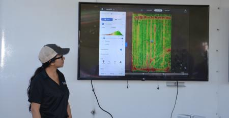 Ana Morales watches a video screen displaying images from a drone