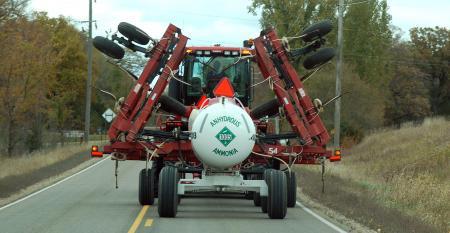 tractor carrying anhydrous ammonia tank driving down rural road