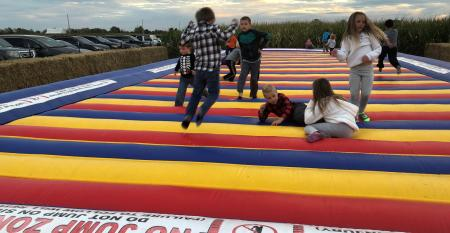 children jumping on inflatable pad on farm