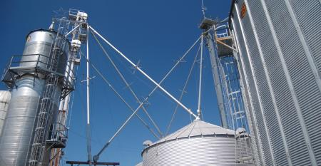 Upward view of grain bins against a blue sky