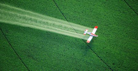 An overhead view of a crop duster spraying agricultural chemicals on a farm field.