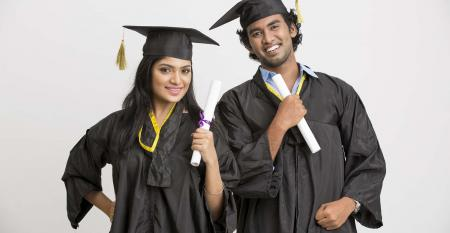 Two college graduates in gowns holding degrees.