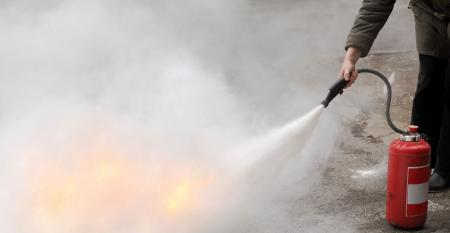 Up close fire fighter spraying flames with fire extinguisher
