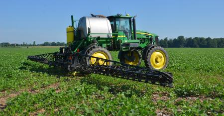 tractor spraying in soybean field