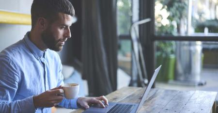 Young man starting working day early in morning drinking coffee using modern laptop computer and wifi