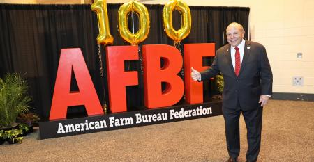 Zippy Duvall standing by banner or balloons celebrating 100th annual convention of AFBF