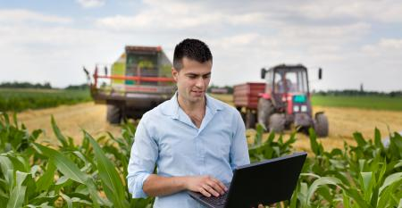 farmer-with-laptop-during-harvest-GettyImages-480915848.jpg